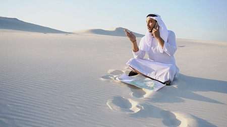 Handsome Arabian UAE Sheikh male businessman talks on mobile with business partner and solves important business issues and problems, holds paper project and makes notes with ballpoint pen, sitting on white clean sand outdoors on summer day. Swarthy Muslim with short dark hair dressed in kandura, long, spacious dress made of white unpainted cotton with knitted lace cap of hafia, on top of which headscarf and dark brown shoes are tied. Concept of Arab and Muslim men, business and business, modern technology and gadgets, united Arab emirates and beautiful landscapes, sheikh in desert and seclusion from nature, national clothing of emirates. Stock Photo