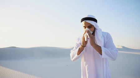 Sad handsome young man, sheikh ill with cold and feels unwell, eases breathing with handkerchief and looks to side, standing in middle of bottomless desert with snow-white sand on sunny summer day. Swarthy Muslim with short dark hair dressed in kandura, long, spacious dress made of white, unpainted cotton with knitted lace cap, gafia, over which headscarf tied. Concept of Arab and Muslim men, United Arab Emirates and beautiful landscapes, advertisement of pharmaceuticals and medicines, deteriorated state of health and prevention of treatment of diseases, national clothing of Emirates. Stock Photo