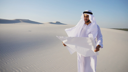 Handsome young Arabian UAE Sheikh male Arab businessman looks at future construction project plan and mentally presents and transports to terrain, looks around and stands in middle of wide desert with white clean sand on clear warm day against blue sky. Swarthy Muslim with short dark hair dressed in kandura, long, spacious dress made of white unpainted cotton with knitted lace cap of hafia, on top of which headscarf and dark brown shoes are tied. Concept of Arab and Muslim men, business and business, United Arab Emirates and beautiful landscapes, sheikh in desert and seclusion from nature, Emirates national costume. Stock Photo