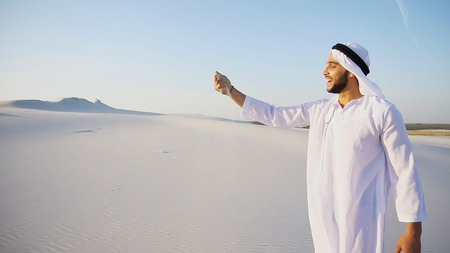Charming young male Arab looks toward sun and goes up sand, examining landscapes of wide desert. Muslim smiles, leans over and takes sand in hands, blowing in wind. Swarthy, handsome Muslim with short dark hair dressed in kandura, long, spacious dress made of white unpainted cotton with knitted lace cap of hafia, on top of which tied goutrail and dark brown shoes. Concept of Arab and Muslim men, united Arab emirates and beautiful landscapes, sheikh in desert and solitude with nature, Emirati national clothes, good mood and happy emotions.