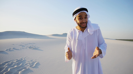 Talkative handsome Muslim Arabian Sheikh man looks with smile at camera and gestures, tells about sights of countries and desert or keeps telecast about travel, standing in middle of bottomless sandy desert with white clean sand against blue sky with hot day outdoors. Swarthy, handsome Muslim with short dark hair dressed in kandura, long, spacious dress made of white unpainted cotton with knitted lace cap of hafia, on top of which tied goutrail and dark brown shoes. Concept of Arab and Muslim men, United Arab Emirates and beautiful landscapes, advertisement of travel company or airline advertising, national clothes of Emirates, good mood and happy emotions.