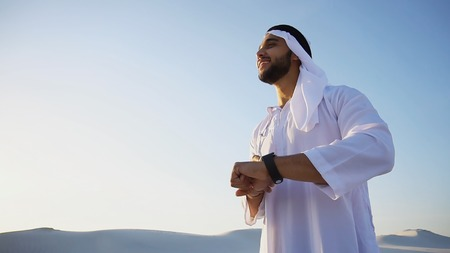 Handsome male Arab tastes coffee drink from white cup and enjoys peaceful morning, smiling and standing in midst of boundless sandy desert with white sand at sunrise on warm summer morning. Swarthy Muslim with short dark hair dressed in kandura, long, spacious dress made of white unpainted cotton with knitted lace cap of hafia, on top of which headscarf and dark brown shoes are tied. Concept of Arab and Muslim men, united Arab emirates and beautiful landscapes, advertisement of travel company, national clothes of emirates, good mood and happy emotions.