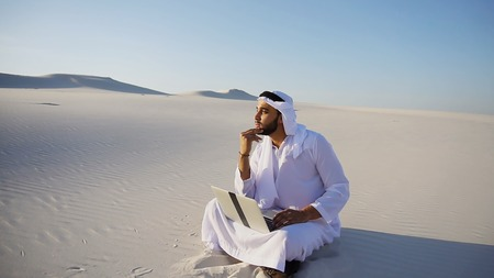 Stately Arabian UAE Sheikh entrepreneur holds in hands and examines project on paper, compares with future site for construction and transfers data to laptop, sitting on white sand in bottomless wide desert in afternoon against blue sky. Swarthy Muslim with short dark hair dressed in kandura, long, spacious dress made of white unpainted cotton with knitted lace cap of hafia, on top of which headscarf and dark brown shoes are tied. Concept of Arab and Muslim men, business and business, modern technology and gadgets, united Arab emirates and beautiful landscapes, sheikh in desert and seclusion from nature, national clothes of emirates. Stock Photo