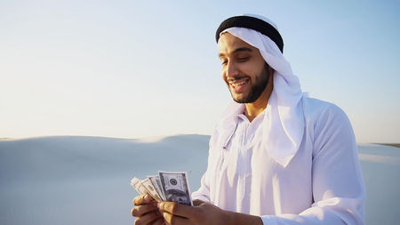 Handsome young Emirate in reckless mood recounts and examines banknotes, can not believe in own happiness or mirage, smiles and laughs throwing money down wind, standing in middle of bottomless desert with white sand on sunny summer day. Swarthy Muslim with short dark hair dressed in kandura, long, spacious dress made of white, unpainted cotton with knitted lace cap, gafia, over which headscarf tied. Concept of Arab and Muslim men, business and finance, smile of fortune and great mood, united Arab emirates and beautiful landscapes, national clothes of Emirates.