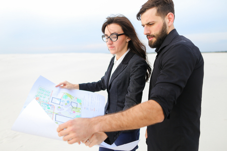 Deputy female and architect male meet to discuss stadium in countryside, people standing in deserted place holding whatman paper with plan smiling looking around. Young bearded man in black shirt and lady in glasses wearing strict suit communicating. Concept of exploring new territories, cooperation or business negotiation.