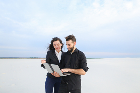 Journalists man and woman use laptop, colleagues preparing reportage about sailing competitions at coast. Bearded fellow and pretty girl with long hair standing among sands discussing work. Concept of innovative technologies, gadgets or business outfits. Reklamní fotografie