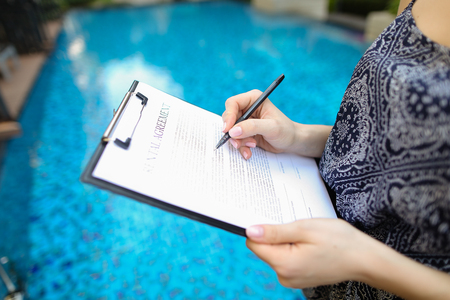 Photographed close hand of girl signing sunny day paper on pool background. concept of signing contract, travel, new contract or arrangement. Front used with Open Font License
