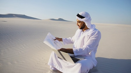 Handsome Arabian UAE Sheikh Arab businessman and construction worker uses computer for design, busy developing complex schemes and opens drawing for checking and clarifying details sitting on white sand in bottomless wide desert in afternoon against blue sky. Swarthy Muslim with short dark hair dressed in kandura, long, spacious dress made of white unpainted cotton with knitted lace cap of hafia, on top of which headscarf and dark brown shoes are tied. Concept of Arab and Muslim men, business and business, modern technology and gadgets, united Arab emirates and beautiful landscapes, sheikh in desert and seclusion from nature, national clothes of emirates.