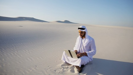 Successful young Arabian UAE Sheikh businessman male Muslim uses laptop to build drawing in Photoshop and prints fingers on laptop sitting on white sand in bottomless wide desert in afternoon against blue sky. Swarthy Muslim with short dark hair dressed in kandura, long, spacious dress made of white unpainted cotton with knitted lace cap of hafia, on top of which headscarf and dark brown shoes are tied. Concept of Arab and Muslim men, business and business, modern technology and gadgets, united Arab emirates and beautiful landscapes, sheikh in desert and seclusion from nature, national clothes of emirates.