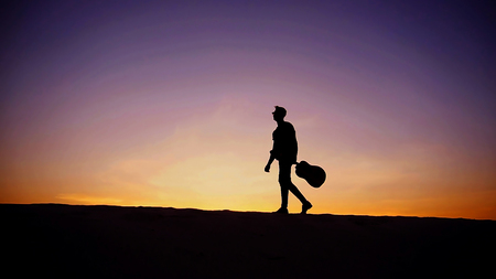 Young Muslim male performer and singer walks through sandy desert with guitar in hands, stops and begins to play on spot on musical instrument, rejoices and smiles, sings songs about love on warm summer evening at sunset. Swarthy man with dark hair and short haircut in sunglasses dressed in camouflage t-shirt, black pants and brown shoes. Concept of handsome Arab young man, hobby or favorite thing to do, learning or playing stringed musical instruments, good mood and positive emotions, beautiful scenery and amazing travel. Banco de Imagens