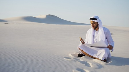 Modern Arabian UAE Sheikh Arab and builder dials on cellular customer to clarify stages of construction and sits with computer on white clean sand outdoors on hot summer day. Smiling Muslim with short dark hair dressed in kandura, long spacious dress of white unpainted cotton with knitted lace cap, gafia over which headscarf and dark brown shoes are tied. Concept of Arab and Muslim men, business and business, modern technology and gadgets, united Arab emirates and beautiful landscapes, sheikh in desert and seclusion from nature, national clothing of emirates. Banco de Imagens