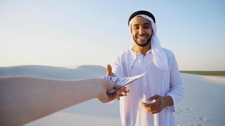 Portrait of emirate male advertising agent or bank employee who, with smile on face, attracts and advertises goods or services of bank, gestures and concludes deal, receives bills that are handed by hand from camera, standing in middle of bottomless sandy desert with white clean sand against blue sky with hot In evening outdoors. swarthy, handsome Muslim with short dark hair dressed in kandura, long, spacious dress made of white unpainted cotton with knitted lace cap of hafia, on top of which tied goutrail and dark brown shoes. Concept of Arab and Muslim men, United Arab Emirates and beautiful landscapes, advertisement of travel company or airline advertising, national clothes of Emirates, good mood and happy emotions.