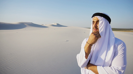 Confident Muslim Arabian UAE Sheikh with serious face puts hand to chin and reflects on future plans, looks into distance and puts hand to forehead defensively against bright sunshine, smiles and rejoices, standing in hot wide desert with white sand on clear summer day. Swarthy Muslim with short dark hair dressed in kandura, long, spacious dress made of white unpainted cotton with knitted lace cap of hafia, on top of which headscarf and dark brown shoes are tied. Concept of Arab and Muslim men, united Arab emirates and beautiful landscapes, sheikh in desert and solitude with nature, Emirati national clothes, good mood and happy emotions.