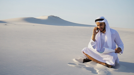 Modern Arabian UAE Sheikh Arab and builder dials on cellular customer to clarify stages of construction and sits with computer on white clean sand outdoors on hot summer day. Smiling Muslim with short dark hair dressed in kandura, long spacious dress of white unpainted cotton with knitted lace cap, gafia over which headscarf and dark brown shoes are tied. Concept of Arab and Muslim men, business and business, modern technology and gadgets, united Arab emirates and beautiful landscapes, sheikh in desert and seclusion from nature, national clothing of emirates. Stock Photo