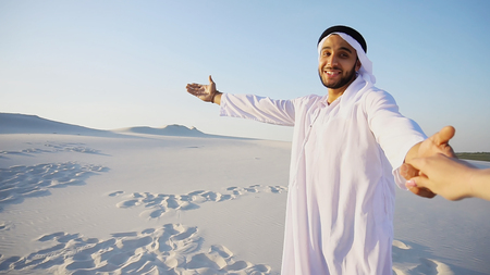 Cheerful Arab male with kindly smile on face leads womans arm from camera and shows desert landscapes, conducts outing in middle of bottomless sandy desert with white clean sand against blue sky in open air. Swarthy, handsome Muslim with short dark hair dressed in kandura, long, spacious dress made of white unpainted cotton with knitted lace cap of hafia, on top of which tied goutrail and dark brown shoes. Concept of Arab and Muslim men, United Arab Emirates and beautiful landscapes, advertisement of travel company or airline advertising, national clothes of Emirates, good mood and happy emotions. Stock Photo