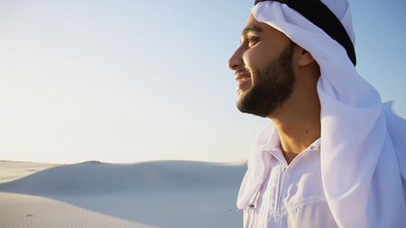 Shooting close-up portrait of attractive and happy Muslim man who enjoys aroma of coffee and drinks from white cup, looking around surroundings and landscapes, standing amidst boundless sandy desert with pure white sand in open air on warm summer morning. Swarthy Muslim with short dark hair dressed in kandura, long, spacious dress made of white unpainted cotton with knitted lace cap of hafia, on top of which headscarf and dark brown shoes are tied. Concept of Arab and Muslim men, united Arab emirates and beautiful landscapes, advertisement of travel company, national clothes of emirates, good mood and happy emotions.