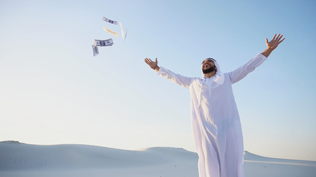 Stately young male Arab man in good mood conducts financial training of money, smiles and laughs joyfully launches money to wind, standing in middle of bottomless desert with white sand on sunny summer day. Swarthy Muslim with short dark hair dressed in kandura, long, spacious dress made of white, unpainted cotton with knitted lace cap, gafia, over which headscarf tied. Concept of Arab and Muslim men, business and finance, smile of fortune and great mood, united Arab emirates and beautiful landscapes, national clothes of Emirates.