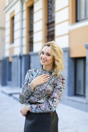 Beautiful female photo model standing near building in background and wearing leather skirt. oncept of vogue and fashion.