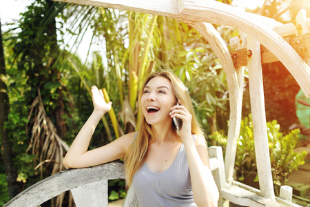 Young woman got great news by talking on smartphone for work on sunny day, background of sunshine green palms in Thailand, Phuket. Concept of new technologies for better life, travel to tropical countries, remote work freelancing