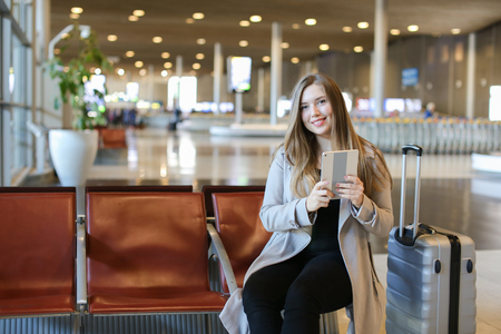 European pretty girl using internet by modern tablet in airport waiting room near grey valise. Concept of social networks, free hotspot and gladden passenger. Imagens