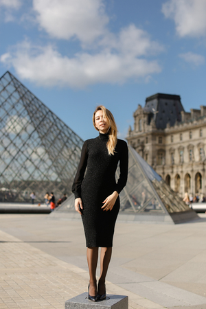 Tiny female person standing near Louvre and glass pyramind in black dress in Paris. Concept of fashion and trip to Franse, European landmarks.