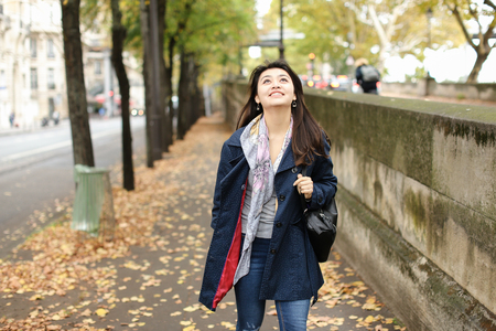 Asian female tourist walking on autumn street with fallen leaves in Europe. Concept of international beauty and foreign student.