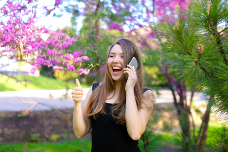 Young girl speaking by smartphone and showing thumbs up in blooming park. Concept of gladden subscriber and good tariff plan, modern technology.