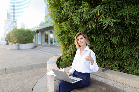 Caucasian female manager working with laptop and papers in open air near green plant, showing thumbs up. Concept of busines, modern technology and working online.