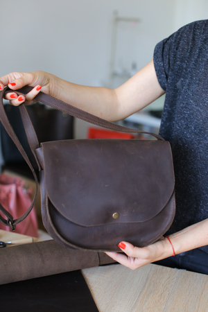 Female person keeping woman brown leather handbag. Concept of home business and handicraft good.