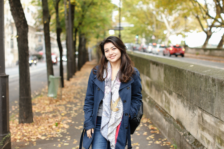 Asian smiling female tourist walking on autumn street with fallen leaves in Europe. Concept of international beauty and foreign student. Stock Photo