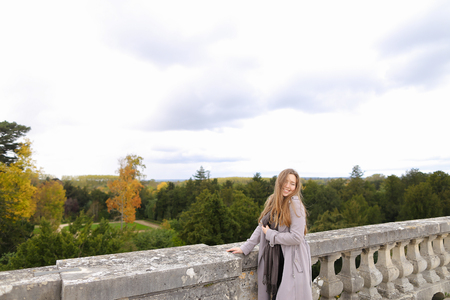 Young caucasian female person standing near concrete railing with green trees background. Concept of architectural elements and visiting Europe. Archivio Fotografico