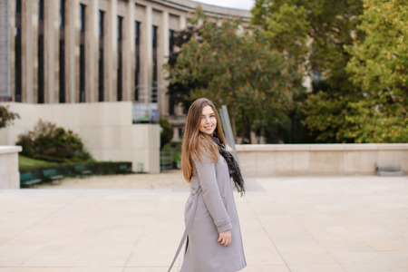 Woman strolling in city near building and wearing grey coat. Concept of traveling to Europe, good weather and positive emotions. Stock Photo