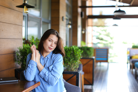 Female young person sitting at cafe in room plants background and wearing jeans shirt. Concept of having break and resting. 版權商用圖片