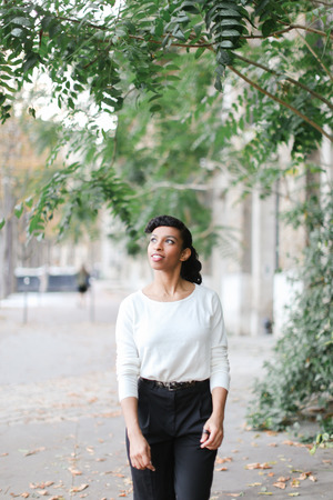 Afro american stylish businesswoman walking in town near green trees and building, wearing white blouse. Concept of black beautiful person and vogue.