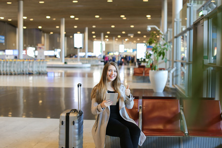 Pretty woman using internet by modern tablet in airport waiting room near grey valise and showing thums up. Concept of social networks, free hotspot and gladden passenger. Banco de Imagens
