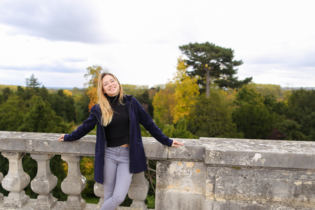 Pretty girl standing near concrete railing with green trees background. Concept of architectural elements and visiting Europe.