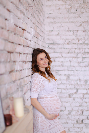 Pregnant woman wearing white dress standing in brick wall background and holding belly. Concept of pregnance and positive emotions.
