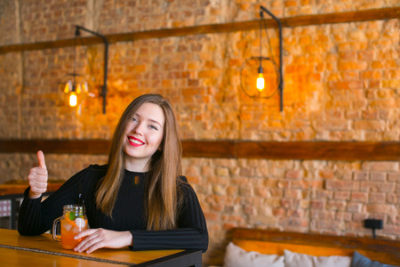 Young woman enjoying nice atmosphere of favorite coffee house, smiling fair-haired lady wearing white blouse sitting near wooden table with glass cup of drink, female looks happy. Concept of free time, weekend, cosiness