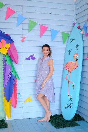 Young pretty pregnant woman standing near surfboard and decorated children house. Concept of pregnance and motherhood, summer.
