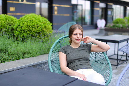 Young woman resting at street cafe and sitting in chair near green plant. Concept of beauty and leisure time in open air.