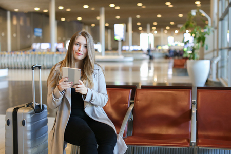 American female person using internet by modern tablet in airport waiting room near grey valise. Concept of social networks, free hotspot and gladden passenger. Imagens