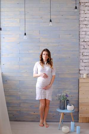 Pregnant woman standing in white dress, wooden wall and lamps in background. Concept of pregnance and interior.