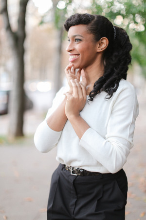 Smiling black girl wearing white blouse and black pants. Concept of beauty and business person. Stock Photo