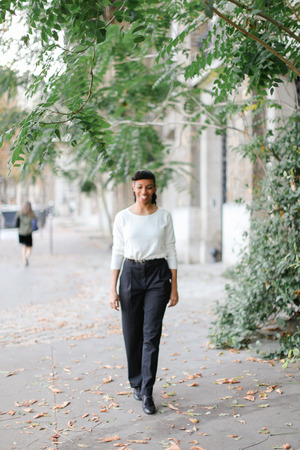 Afro american businesswoman walking in town near green trees and building, wearing white blouse. Concept of black beautiful person and vogue.