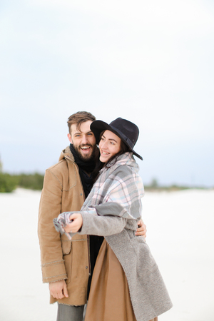 Happy young woman and man wearing coats and scarfs standing in winter snow background. Concept of happy couple and positive emotions.