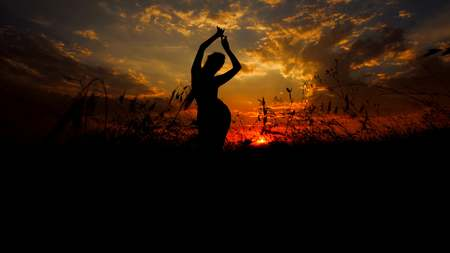 Female person black silhouette doing asanas in steppe, sunset background. Concept of yoga practise and relaxing.