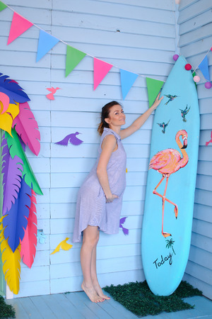 Young caucasian pregnant woman standing near surfboard and decorated children house. Concept of pregnance and motherhood, summer.