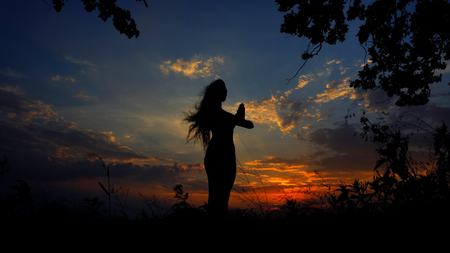 Dark female silhouette praying in evening sky background. Concept of relaxing and doing yoga asanas.