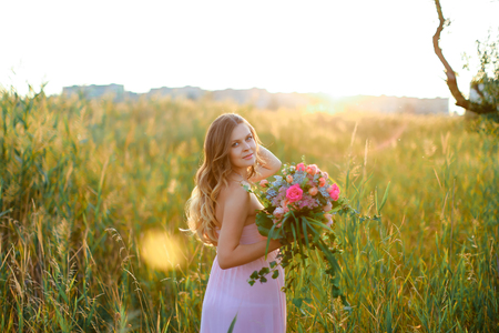 Pregnant young caucasian woman wearing pink dress with bouquet of flowers standing in steppe background with sun rays. Concept of photo session, pregance and summer inspiration.
