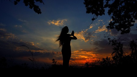 Dark female silhouette doing yoga and meditating in evening sky background. Concept of relaxing before sleeping and asanas.